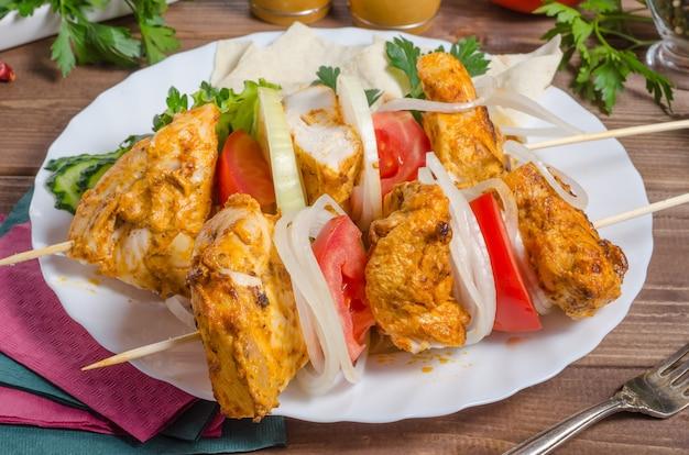 Brochette de poulet aux oignons et tomates sur un gros plan de plaque blanche
