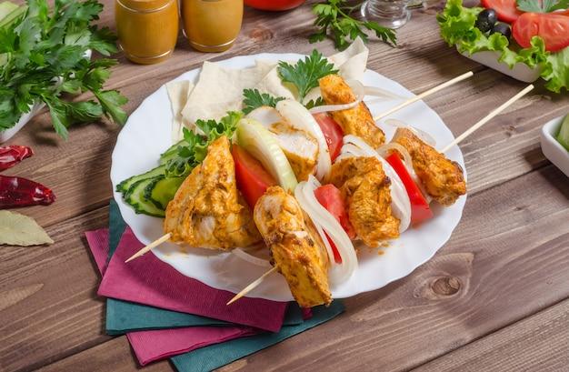 Brochette de poulet aux oignons et tomates sur une plaque blanche sur fond de bois foncé