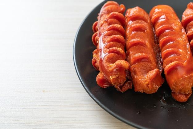Brochette de saucisses frites sur plaque noire