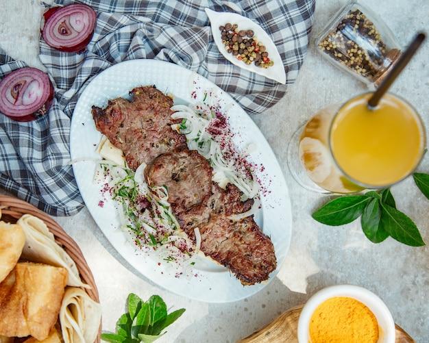 Brochette de viande caucasienne avec salade d'oignons et jus d'orange.