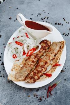 Brochette de viande avec du ketchup sur une plaque blanche.
