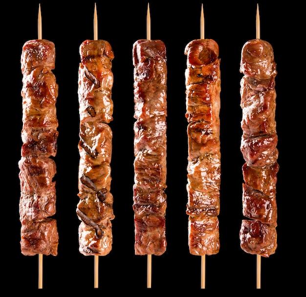 Brochette de viande sur un espace noir.