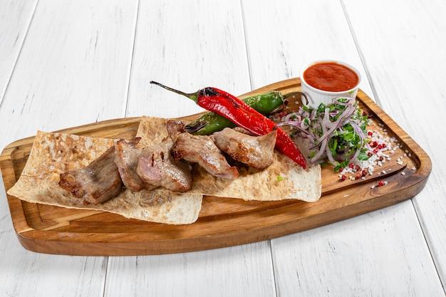Brochette de viande grillée avec légumes et sauce rouge sur un bureau en bois
