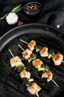 Brochettes - brochettes de viande grillée, shish kebab avec des légumes. fond noir. vue de dessus