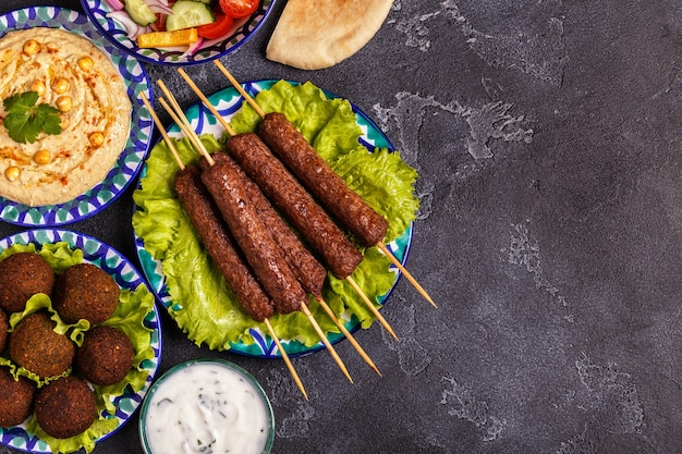 Brochettes classiques, falafel et houmous dans les assiettes.