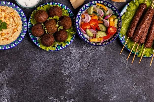 Brochettes classiques, falafel et houmous dans les assiettes