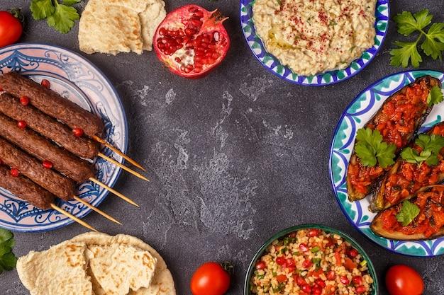 Brochettes classiques, salade de taboulé, baba ganush et aubergines cuites au four avec sauce.