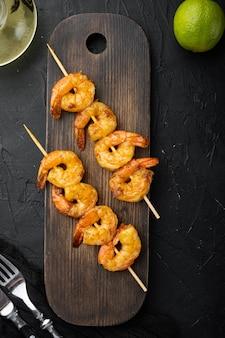 Brochettes de crevettes épicées savoureuses brochettes sriracha avec lime, sur planche de service en bois, sur fond noir