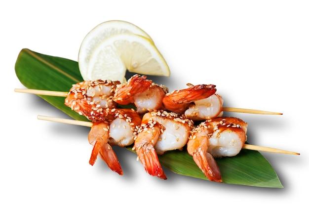 Brochettes de crevettes sur une feuille de bambou