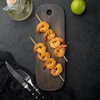 Brochettes de crevettes grillées. fruits de mer, étagères. brochettes de crevettes crevettes aux herbes, sur planche de service en bois, sur fond noir