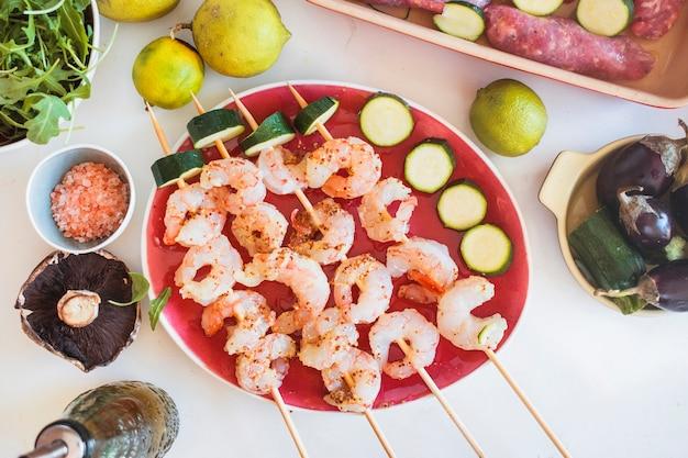 Brochettes de crevettes servies avec des légumes et des fruits