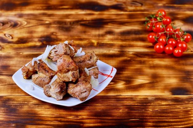 Brochettes cuites avec des légumes et des épices sur une planche de bois