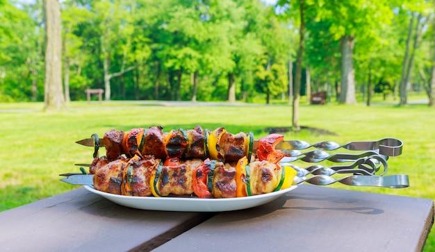 Brochettes grillées sur l'assiette à base de poulet au porc, bacon et légumes.
