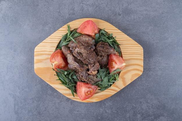 Brochettes grillées et tranches de tomates sur plaque de bois.