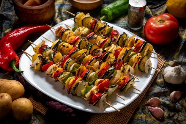 Brochettes de légumes dans une assiette blanche avec des ingrédients crus autour