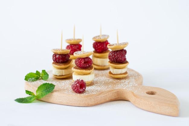 Brochettes de nourriture à la mode avec mini crêpes, framboise, banane et sucre en poudre isolé sur fond blanc