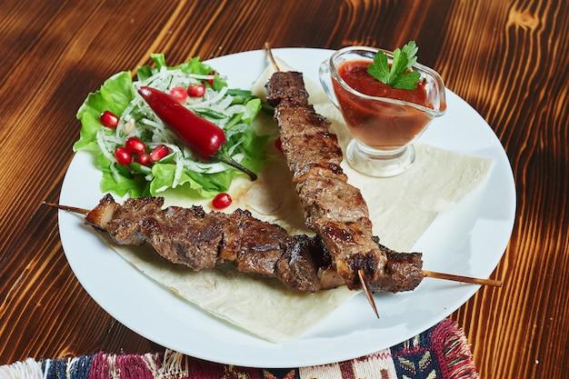 Brochettes de porc en cubes maigres au barbecue, servies avec une tortilla de maïs et de la laitue fraîche et de la salade de tomates, vue rapprochée