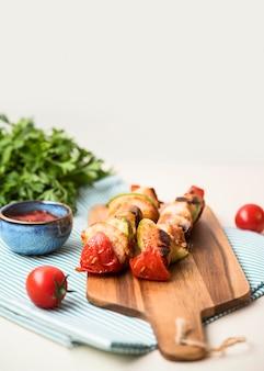 Brochettes de poulet à angle élevé sur une planche à découper avec tomate