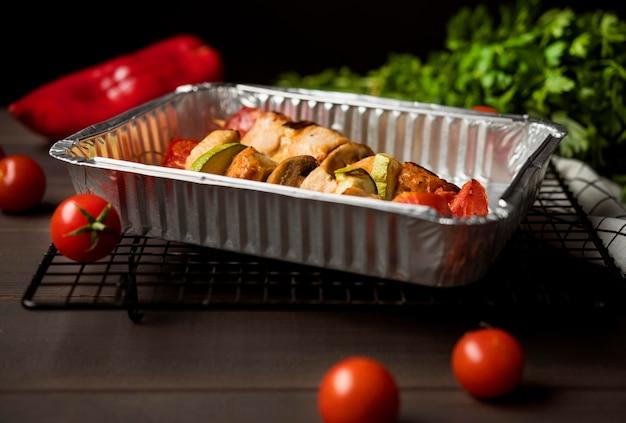 Brochettes de poulet à angle élevé sur plateau avec poivrons rouges et tomates cerises