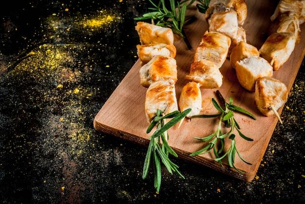 Brochettes de poulet au romarin sur fond métallique rouillé noir