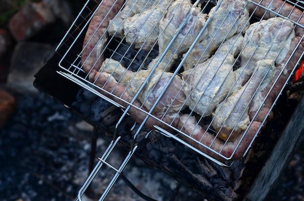 Des brochettes de poulet aux ailes de poulet sont frites dans le champ