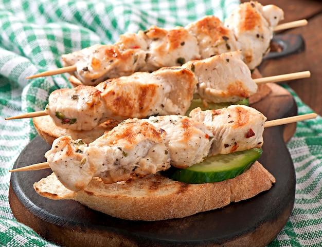 Brochettes de poulet sur des brochettes avec du pain grillé