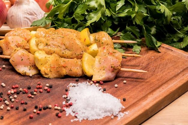Brochettes de poulet crues marinées au citron sur une planche de bois