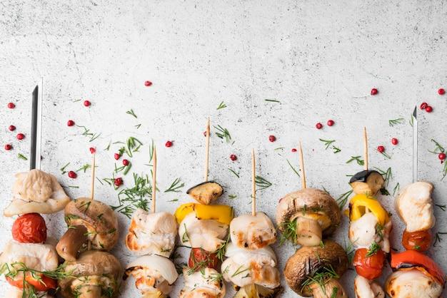 Brochettes de poulet grillé et légumes alignés