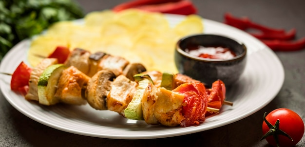 Brochettes de poulet en gros plan avec sauce et frites