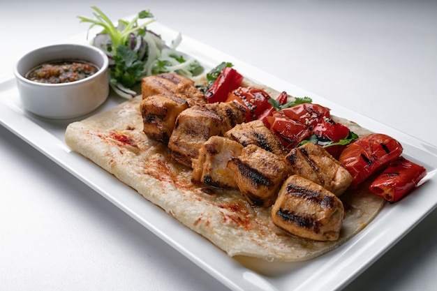 Brochettes de poulet sur pain pita avec sauce à l'oignon mariné et poivron cuit au four sur une plaque blanche sur une plaque blanche