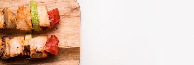 Brochettes de poulet à plat sur une planche à découper avec copie-espace
