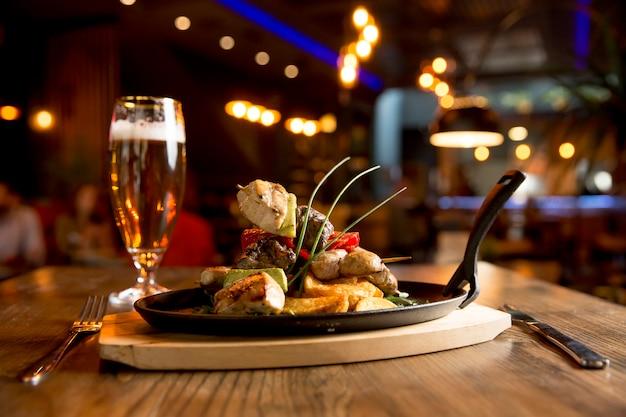 Brochettes de poulet, de porc et de boeuf avec légumes et pommes de terre épicées
