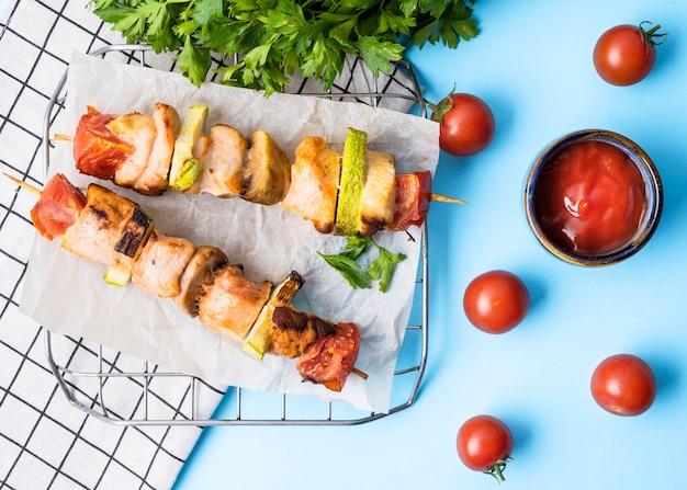Brochettes de poulet vue avant sur papier sulfurisé avec tomates cerises et sauce