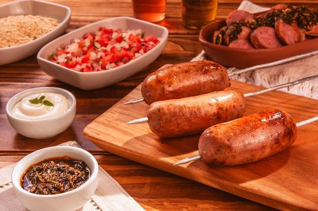 Brochettes de saucisses de porc grillé bbq sur planche à découper en bois avec chimichurri