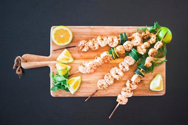 Brochettes de shish aux fruits de mer servies avec des agrumes