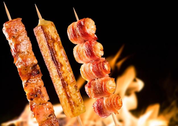 Brochettes de steak assorties sur des flammes de feu.