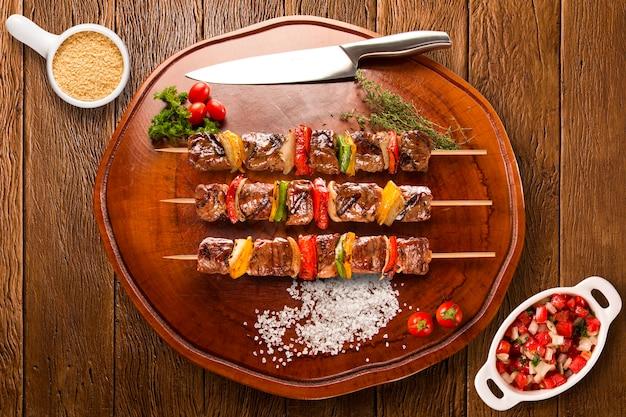 Brochettes de steak sur une planche avec vinagrete et farine de maïs