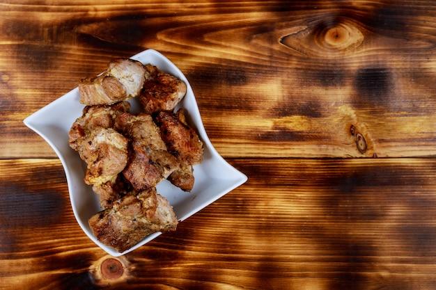 Brochettes de viande et de légumes grillés sur une planche à découper en bois