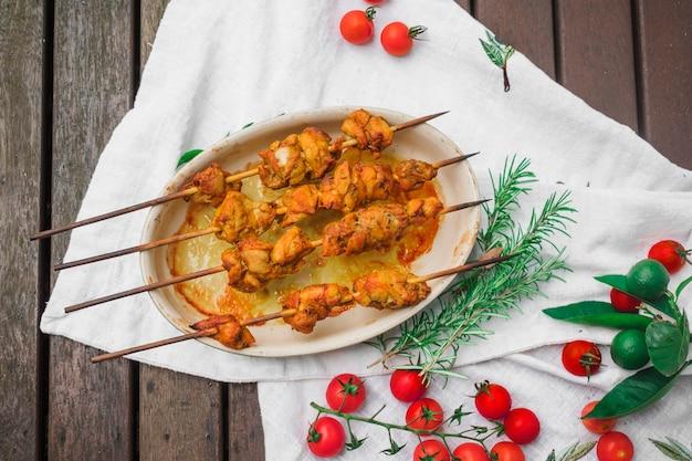 Brochettes de viande servies sur une table avec des tomates