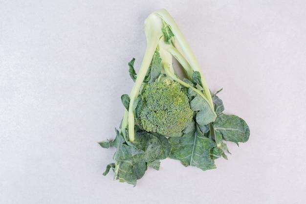 Brocoli biologique avec des feuilles sur une surface blanche