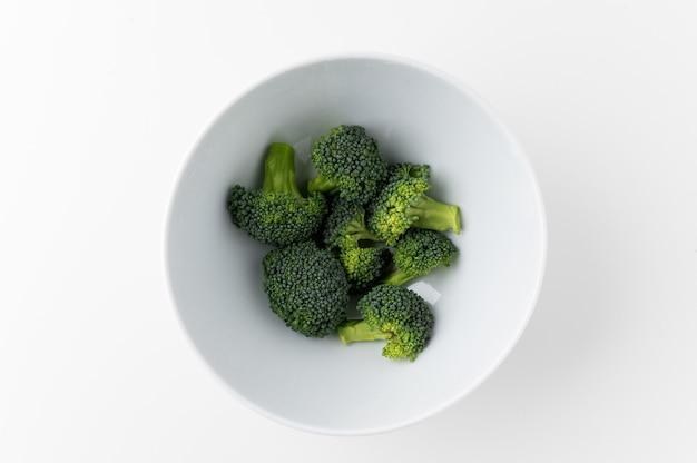 Brocoli cru coupé en petits morceaux et mis dans un bol blanc