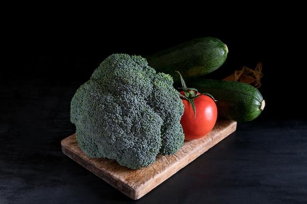 Brocoli frais, courgettes et une tomate sur une planche à découper sur une table noire, style rustique, touche foncée