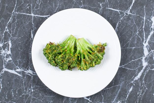 Brocoli frais cuit à la vapeur sur plaque blanche.