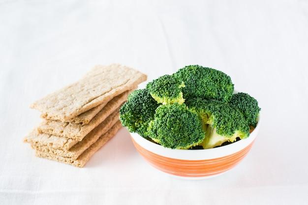 Brocoli frais dans un bol et pain croustillant aux grains sur une table sur un chiffon