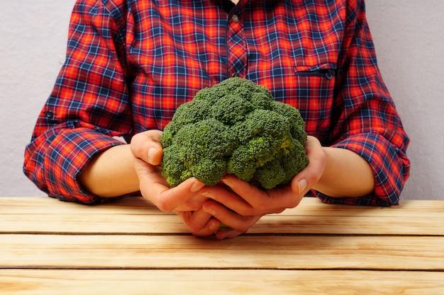 Brocoli frais vert dans les mains des femmes, vêtu d'une chemise à carreaux rouge sur un fond de table en bois