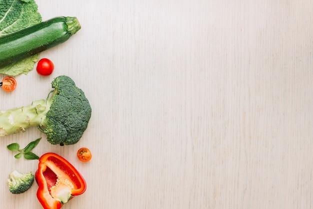 Brocoli; poivron coupé en deux; tomates cerises et courgettes sur une surface en bois crème