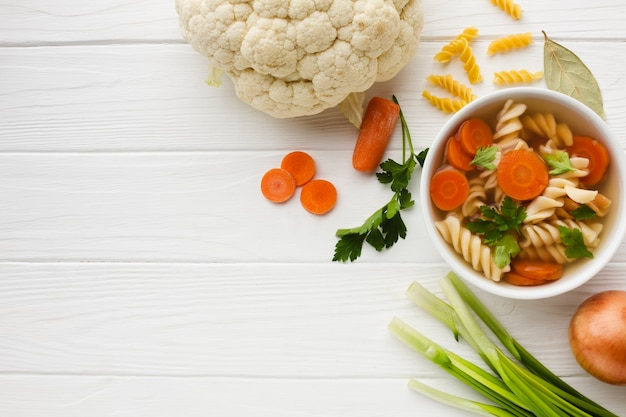 Brocolis et carottes fusilli à plat dans un bol avec espace de chou-fleur et copie