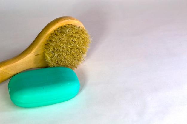 Brosse de bain avec du savon sur fond blanc