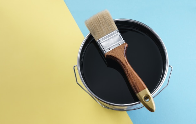 Brosse en bois sur boîte de peinture de couleur noire sur fond bleu et jaune avec espace de copie