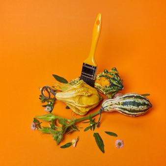 Brosse, citrouilles décoratives, feuilles et fleurs sur fond orange. composition d'automne